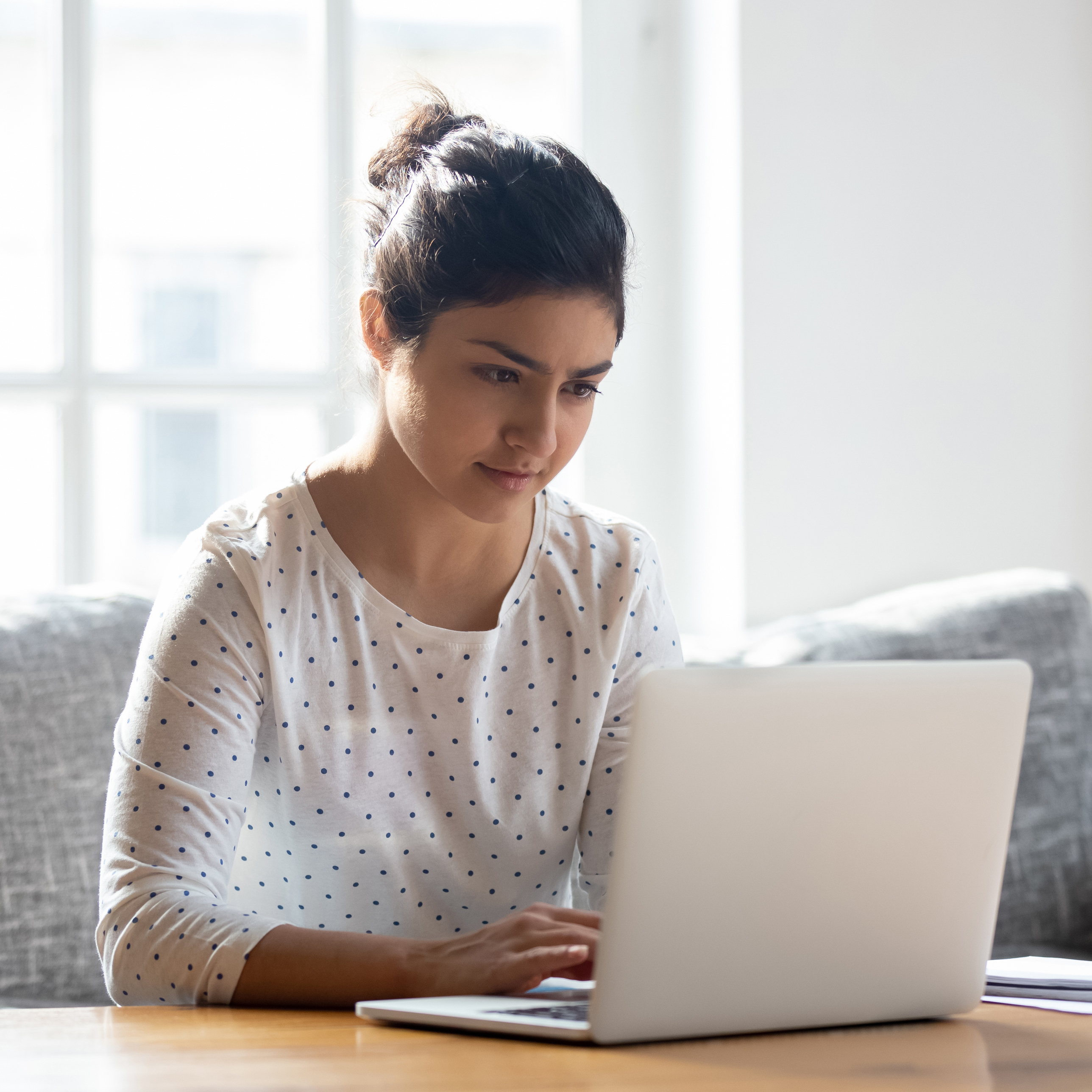 woman sitting at table looking at laptop
